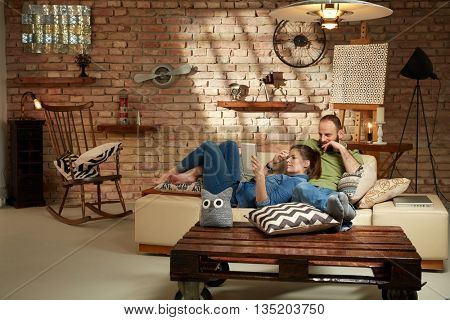 Young couple relaxing at home, using tablet.