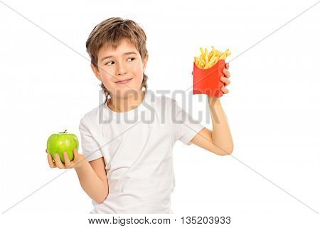 A nine year old boy making choice between fast food french fries and fresh apple. Concept of healthy and unhealthy food. Isolated over white.