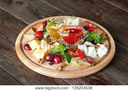 Fruits and cheese oh catering platter top view. Wooden board with variety of cheese and fruits with red and yellow sauces on dark wooden background. Wine snack set