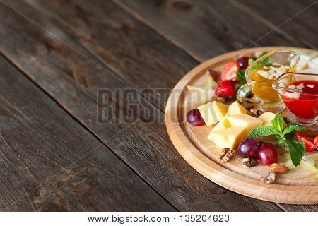 Cheese with grapes and sauces on wood copyspace. Catering platter with gouda cheese, grapes and red and yellow sauces, decorated with mint and nuts