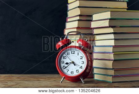 Stack of books and red alarm clock on a background of a school blackboard. Back to school. Left empty space for Your text.