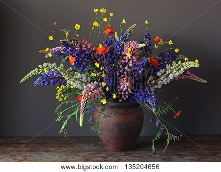 Still life bouquet with lupine and buttercups in a clay jug on a dark background.