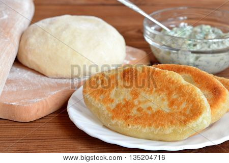 Delicious fried pies on a plate. Dough and rolling pin on a kitchen cutting board. Cheese filling with dill in a glass bowl. Ingredients for cooking homemade pies. Wooden background