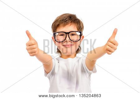 Cheerful smart boy in big glasses looking at the camera and showing thumb. Education. Studio shot. Isolated over white.