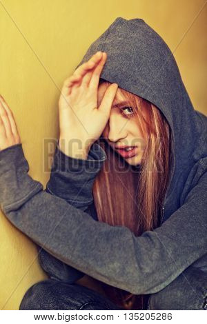 Abused teenage woman trying to hide and defend herself