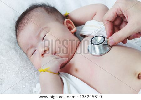 Pediatrician Examining Infant. Two Months Baby Asian Girl Lying On Sickbed In Hospital.