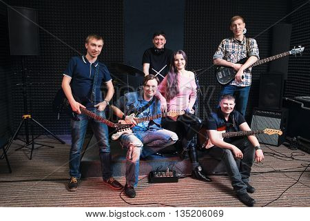 Group photo of student music band. Smiling at camera male musicians and woman vocalist. Music band members posing on stage with their musical instruments. large group of people