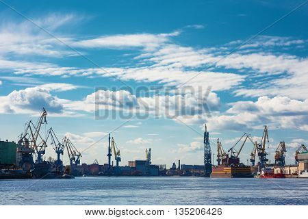 Industrial panorama with cranes and docks. Blue sky. Big Neva River in St.Petersburg, Russia