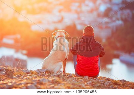 Enjoying sun. Pensive young man sitting on the hill with his dog (yellow labrador retriever). Amazing sunrise in the city. Prague in Czech Republic.