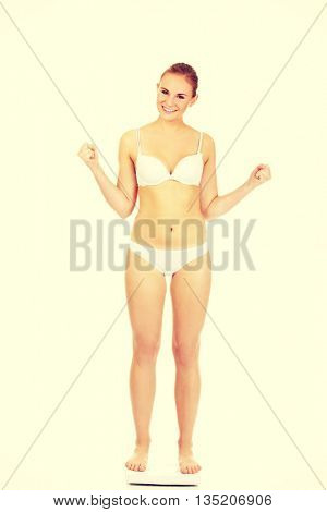 Happy woman standing on scales