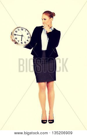 Yawning business woman holding office clock