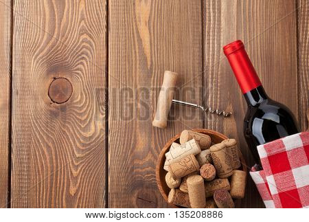Red wine bottle, bowl with corks and corkscrew. View from above over rustic wooden table background with copy space