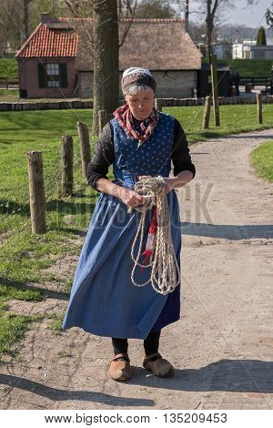 ENKHUIZEN, NORTH-HOLLAND / THE NETHERLANDS - APRIL 11, 2016: Actress in a national dress  with a rope in her hands in an open-air museum of the city of Enkhuizen