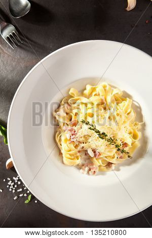 Fettuccine Carbonara with Parmesan on Black Stone Background
