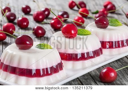 Italian dessert of cherry juice and sweetened cream thickened with gelatin and and molded on a rectangular dish with cherries on a dark wooden background close-up
