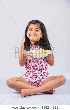 Happy Asian child eating delicious noodle, cheerful little indian girl posing with noodles in white dish isolated over white background, girl eating noodles