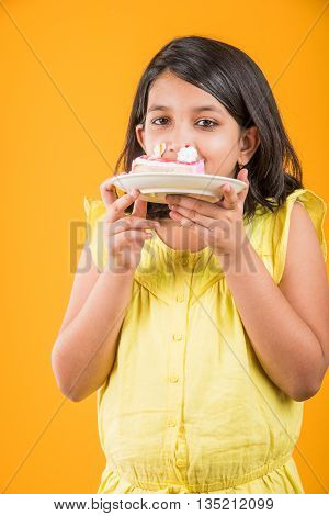 portrait of Indian kid eating cake or pastry, cute little girl eating cake, girl eating strawberry cake or pastry over yellow background