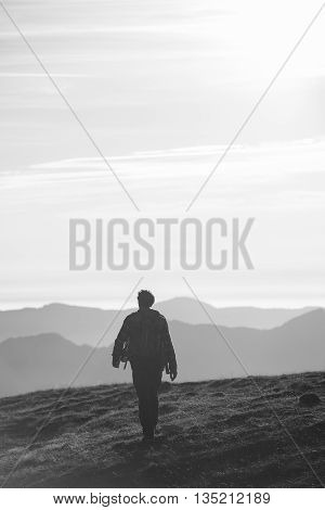 Lonely man walking on the high-altitude meadows with a backdrop of mountains. Black and white