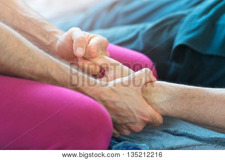 Massager with the finger of the hand stretching in the oustdoor