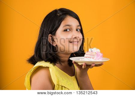 portrait of Indian kid eating cake or pastry, cute little girl eating cake, girl eating strawberry cake over yellow background
