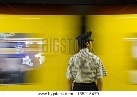 TOKYO, JAPAN - June 20 2016: Subway attendant and fast moving train. The Tokyo subway system handles 8 million passengers per day. In Tokyo, Japan 2016
