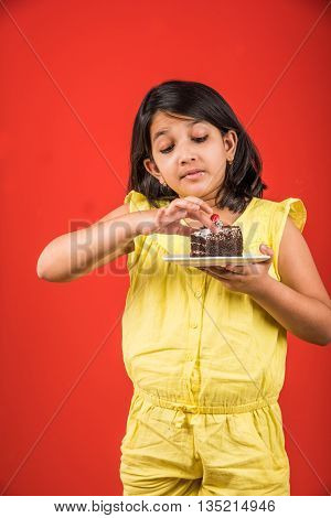portrait of Indian kid eating cake or pastry, cute little girl eating cake, girl eating cake over colourful background