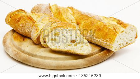 a baguett on wooden board with light dough cut on white background