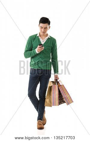 Asian young man holding shopping bags and using cellphone, full length portrait isolated.