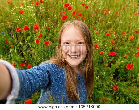 Funny little girl doing selfie in poppy field. Preteen 8-9 years old girl taking photos of herself