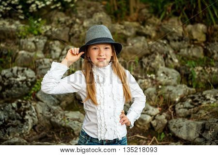 Portrait of pretty little girl of 8-9 years old in garden. Kid girl wearing white vintage blouse and grey black hat