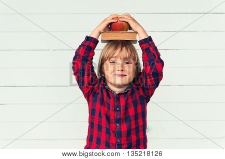 Happy little schoolboy with book and red apple on his head, wearing red and blue plaid shirt, standing against white wooden background. Back to school concept
