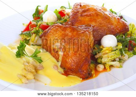 Chicken leg with salad and asparagus on white plate