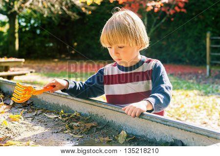 Little boy playing in muddy sandbox on sunny day