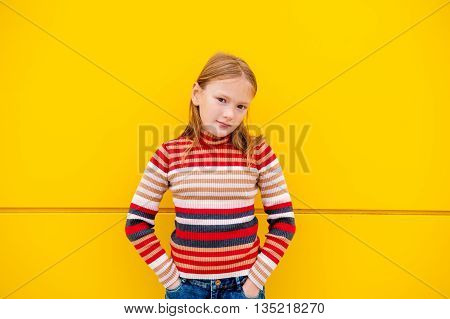 Portrait of a cute little girl of 8 years old, wearing stripe roll neck pullover and denim skirt, standing next to bright yellow wall