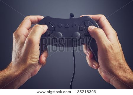 Man using game pad controller to play entertaining electronics video games gaming and entertainment concept