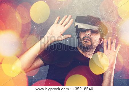 Scared adult man wearing virtual reality goggles and enjoying in scary 3D VR multimedia content