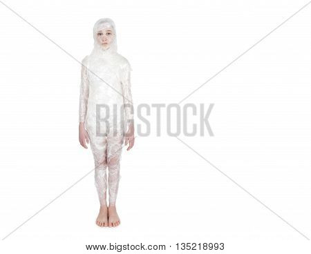 Little girl standing wrapped in transparent film like a mummy on a white background