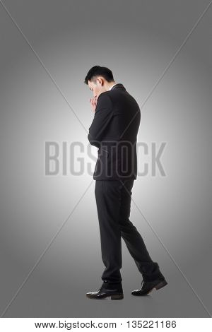 Confused young business man standing and thinking, full length portrait isolated