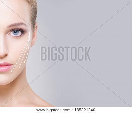 Half face portrait of attractive girl with beautiful blue eyes and arrows on face over grey background. Face lifting concept.