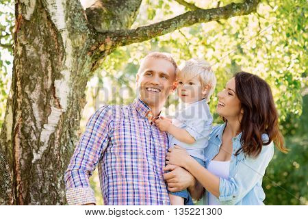 Young couple spending time together with their toddler son. Father holding son.