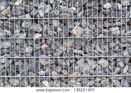 Gabion filled with thick stones; Metal Stone basket with large natural stones for external landscaping.