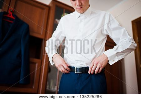 A young man wearing a belt groom preparing for the wedding day