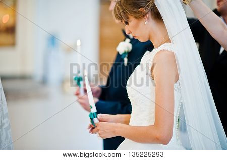 Wedding Couple Holding Candles With Green Ribbons At Church