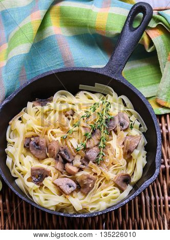 Tagliatelle with mushrooms and onions in a creamy sauce. Dish of Italian cuisine. A tasty dinner. Selective focus