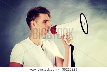 Young man shouting in megaphone.