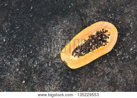 Close up on the half cut of fresh ripe papaya on dark stone.