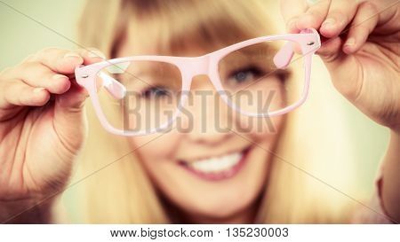 Happy young woman girl holding glasses. Smiling female in studio.