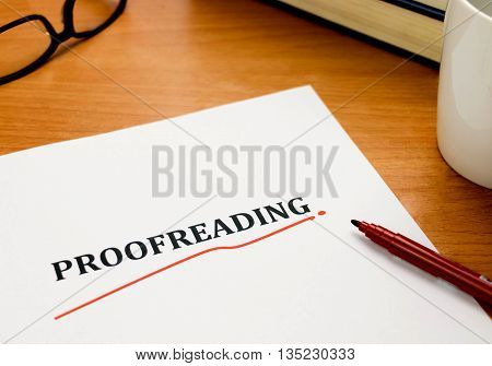 proofreading word on white sheet with red pen book glasses on wooden table