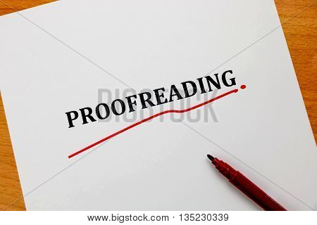 proofreading word on white sheet with red pen on wooden table