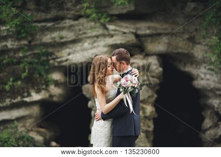 Happy wedding couple hugging and smiling each other on the background gorgeous plants in castle.
